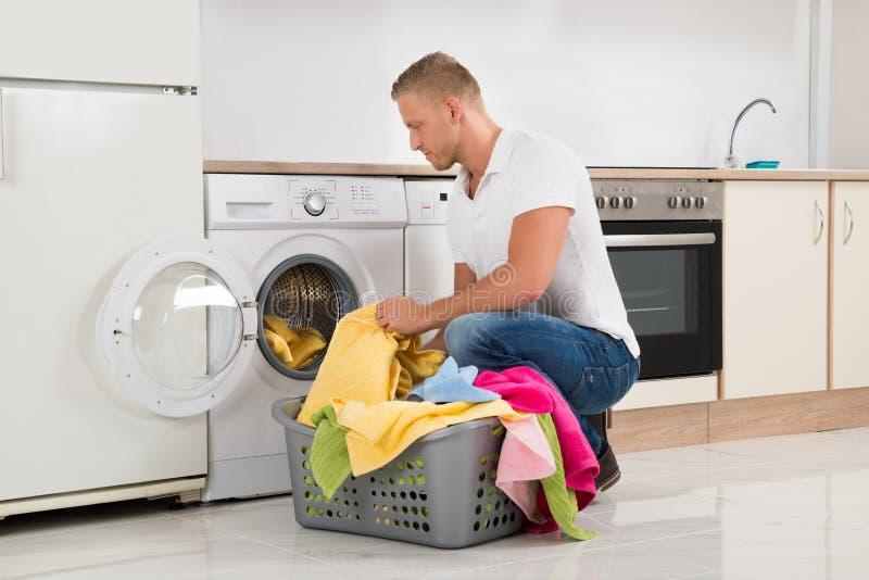 Equipe a colocação da roupa suja na máquina de lavar imagem de stock royalty free