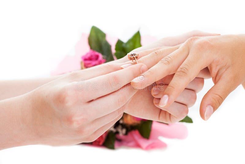 Equipe a colocação de um anel dourado sobre a mão da mulher foto de stock royalty free