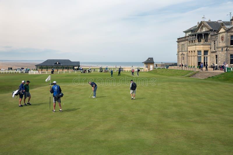 Equipe a colocação de uma bola no campo de golfe famoso StAndrews, Escócia imagem de stock royalty free