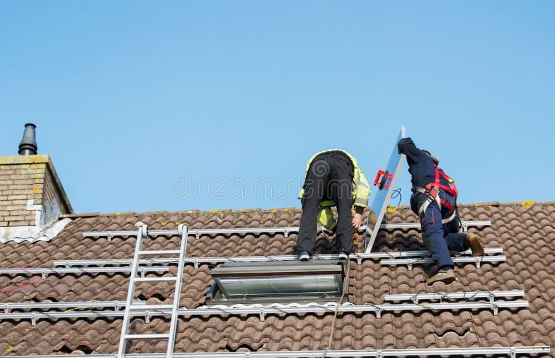 Equipe a colocação do painel solar sobre o telhado imagem de stock royalty free
