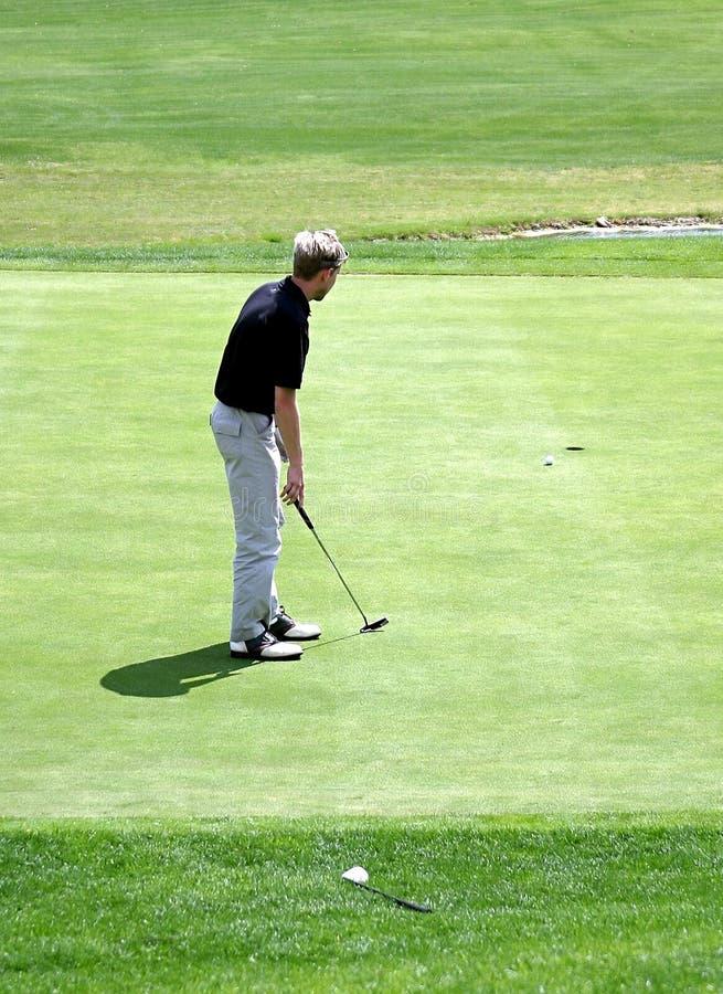 Equipe a colocação sobre o verde durante o jogo do golfe foto de stock royalty free
