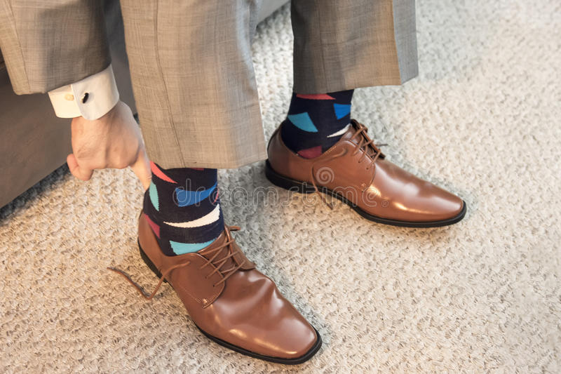 Equipe a colocação sobre sapatas de vestido marrons no vestuário formal com peúgas coloridas fotografia de stock