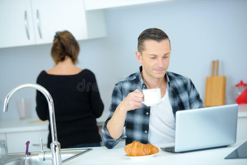 Equipe comer o petisco ao trabalhar com o portátil na cozinha fotografia de stock royalty free