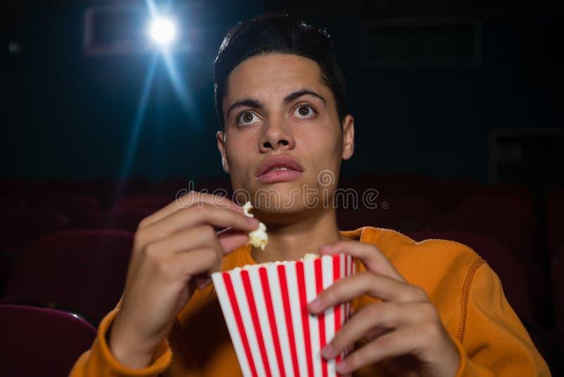 Equipe comer a pipoca ao olhar o filme no teatro imagens de stock