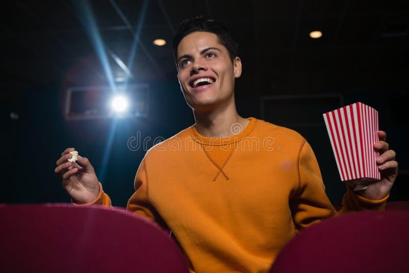 Equipe comer a pipoca ao olhar o filme no teatro imagem de stock royalty free