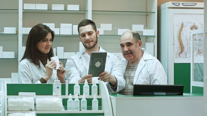 Equipe competente da farmácia com os técnicos do farmacêutico e da farmácia que têm o bate-papo video com os colegas que usam a t imagens de stock