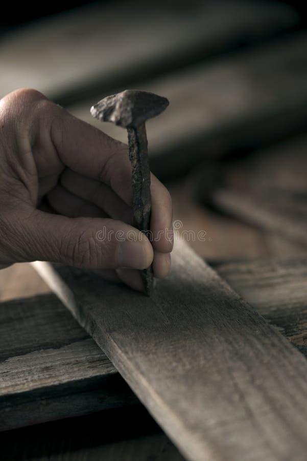 Equipe a condução de um prego em uma cruz de madeira imagem de stock