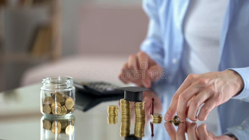 Equipe a contagem da renda, salvar o dinheiro para o estudo, cuidados sobre o futuro das crianças fotos de stock