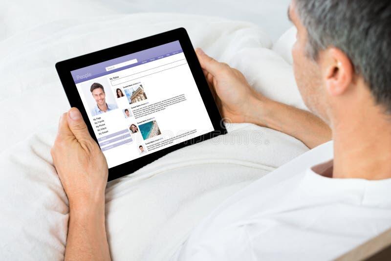 Equipe a conversa em sites de rede sociais usando a tabuleta digital foto de stock