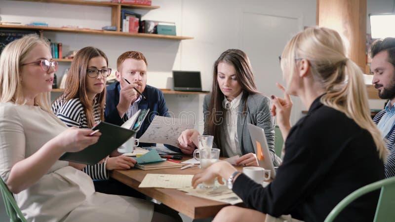 Equipe criativa do negócio na tabela em um escritório startup moderno O líder fêmea explica os detalhes do projeto fotos de stock royalty free