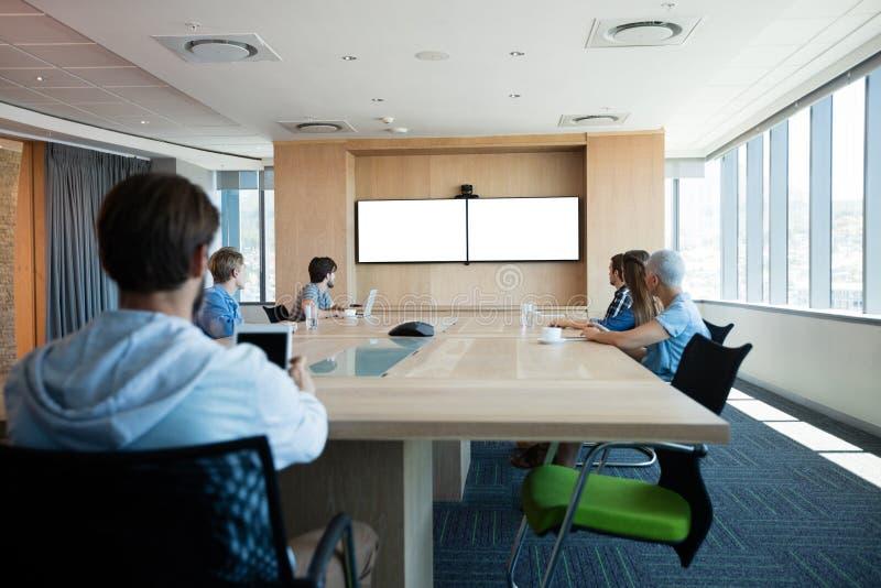 Equipe criativa do negócio que atende a uma chamada video na sala de conferências foto de stock royalty free
