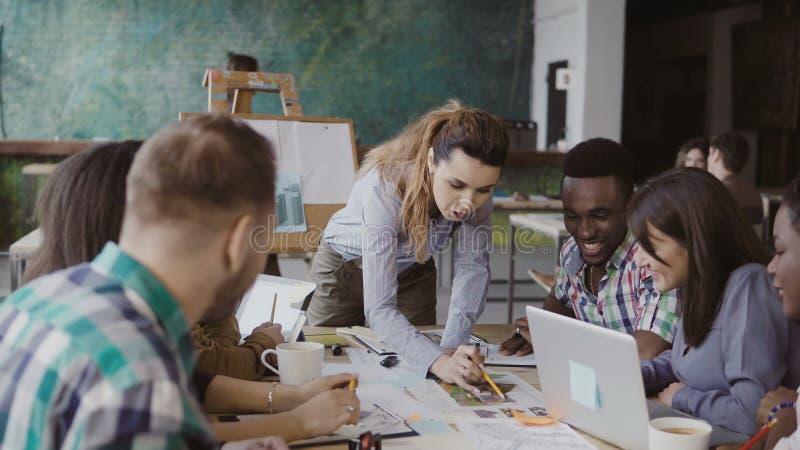 Equipe criativa do negócio que discute o projeto arquitetónico Sessão de reflexão do grupo de pessoas da raça misturada no escrit imagens de stock