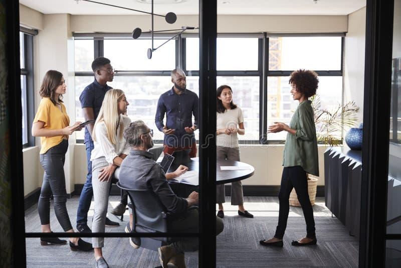 Equipe criativa do negócio que escuta seu colega fêmea que apresenta em uma reunião do clique imagem de stock