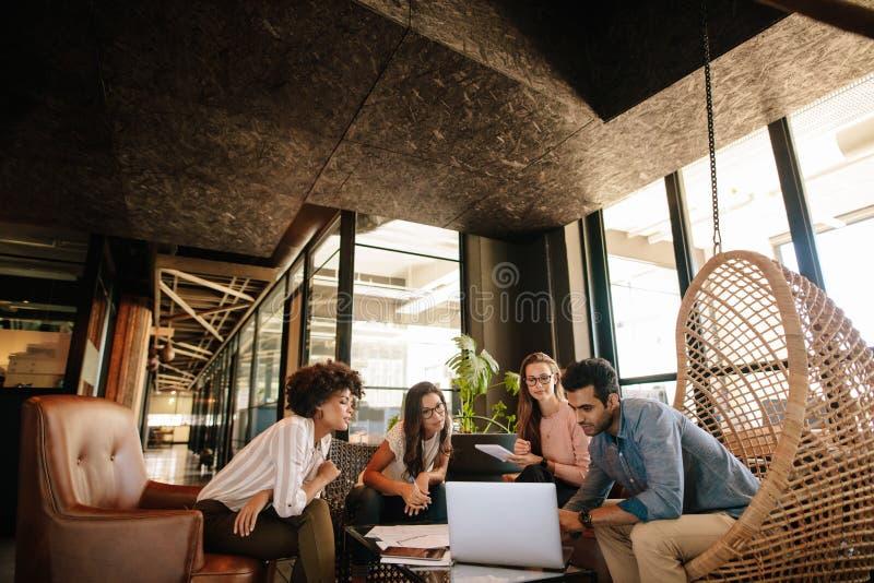 Equipe criativa do negócio que usa o portátil durante a reunião foto de stock royalty free