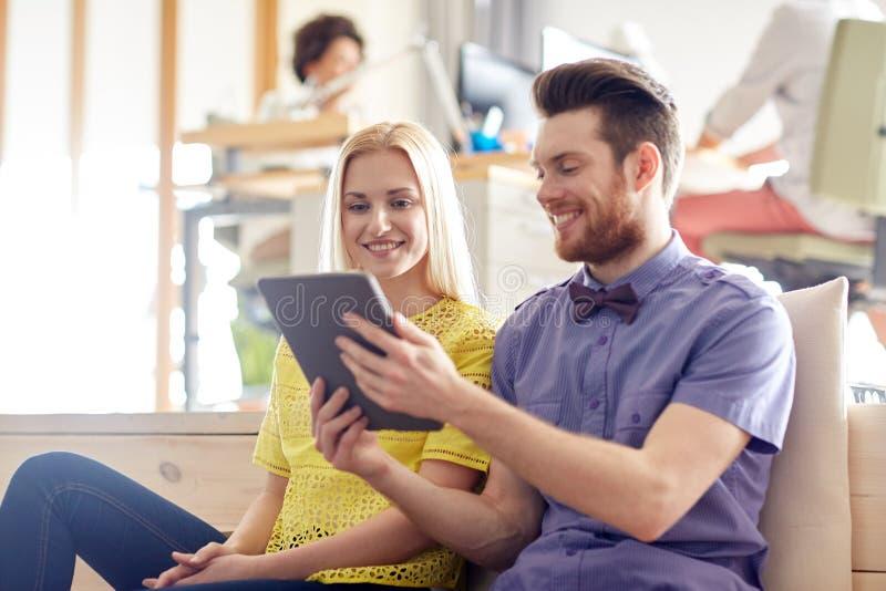 Equipe criativa feliz com o PC da tabuleta no escritório foto de stock