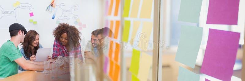 Equipe criativa milenar em torno da tabela e da transição pegajosa da nota foto de stock