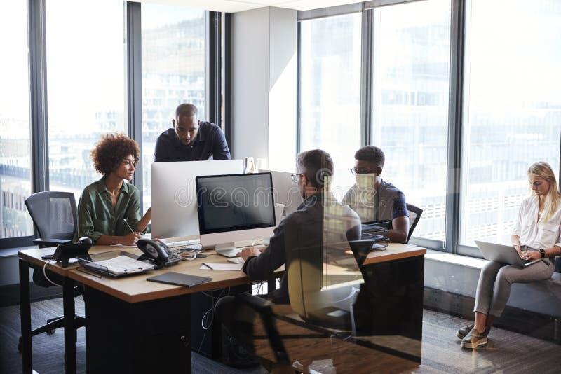 Equipe criativa nova que trabalha junto em computadores em um escritório ocasional, parede de vidro completamente vista fotografia de stock