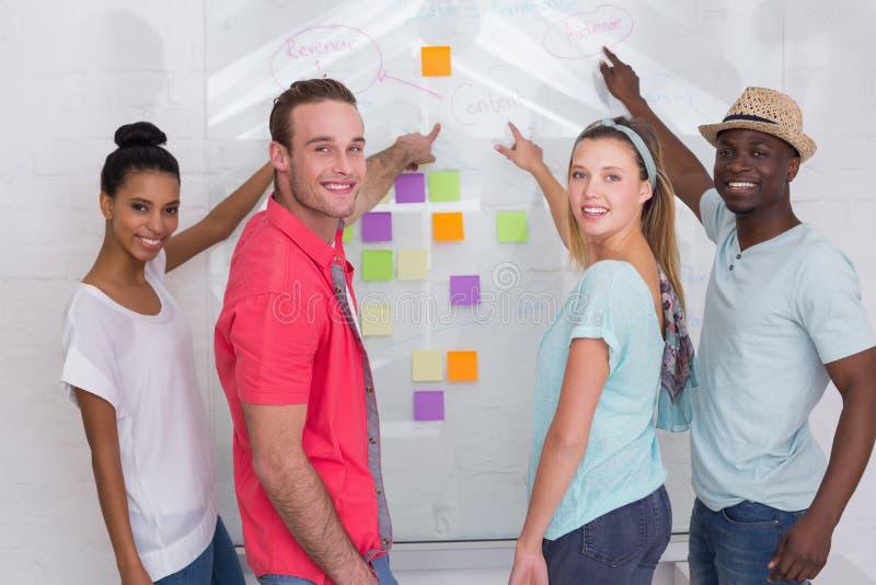 Equipe criativa que aponta em notas pegajosas imagens de stock royalty free