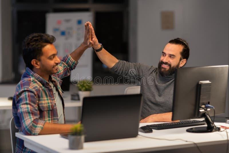 Equipe criativa que faz a elevação cinco no escritório da noite fotografia de stock royalty free