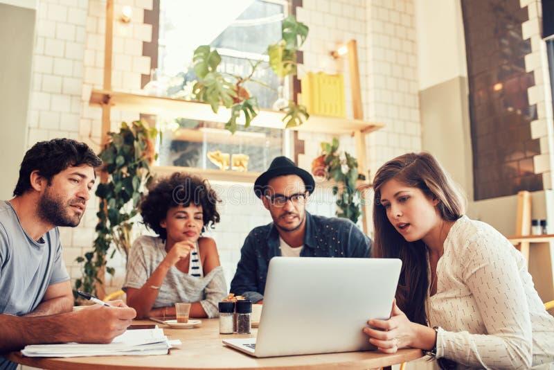 Equipe criativa que senta-se no café e que olha um portátil imagens de stock royalty free