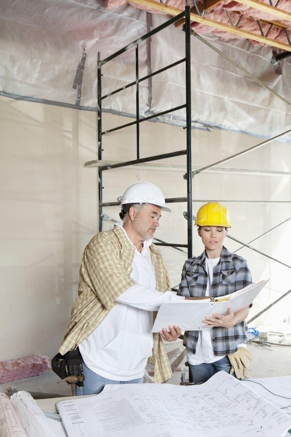Equipe da construção que olha o papel com os modelos na tabela foto de stock