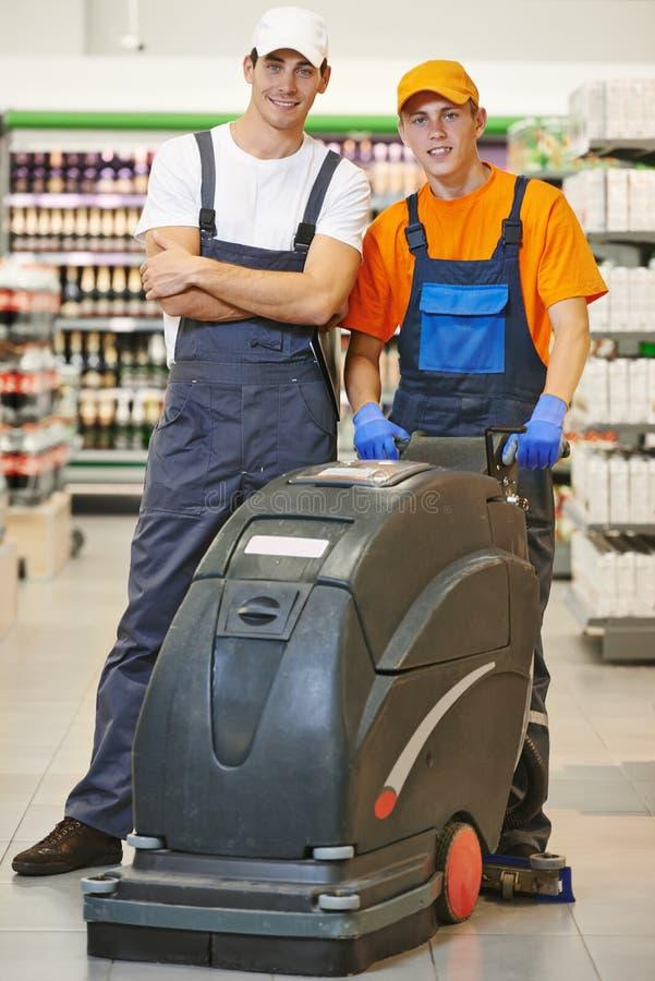 Equipe da limpeza com a máquina na loja fotos de stock