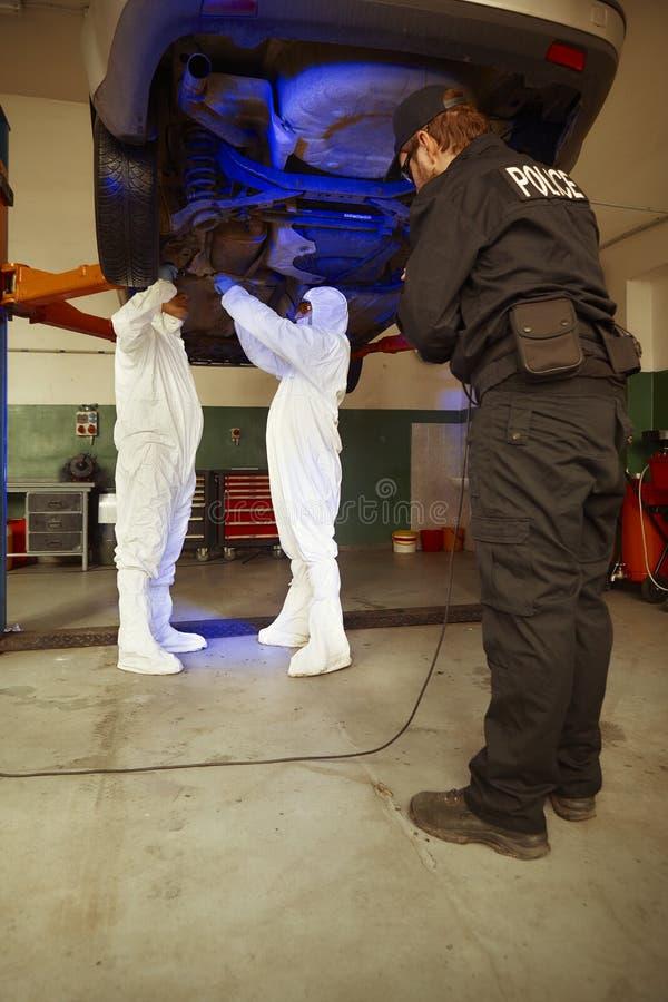 Equipe da polícia que trabalha na luz ultravioleta na coleta dos traços e das evidências fotografia de stock royalty free