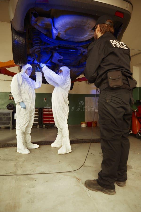 Equipe da polícia que trabalha na luz ultravioleta na coleta dos traços e das evidências fotografia de stock