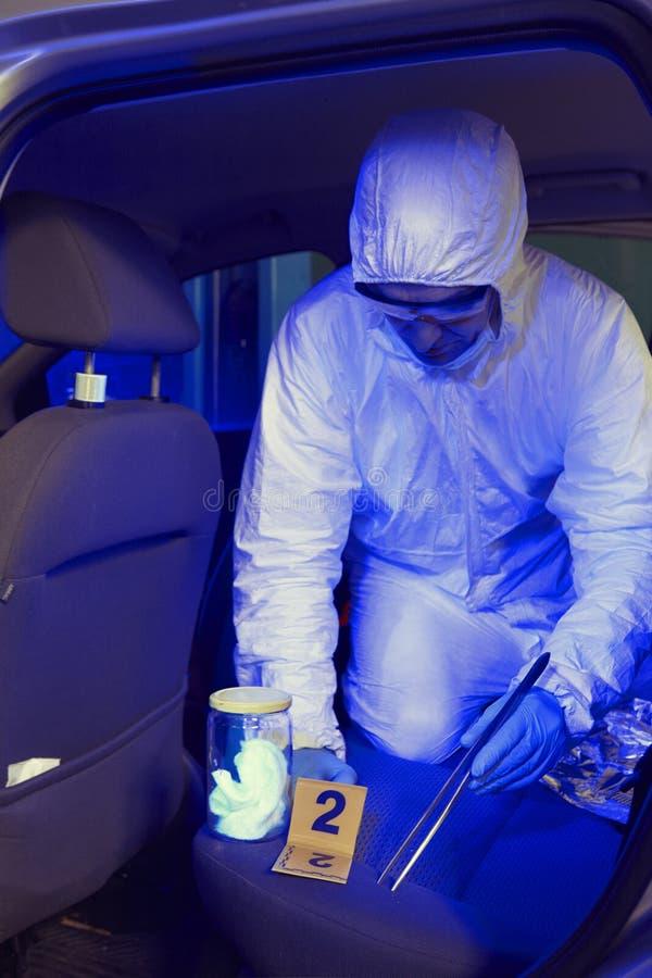Equipe da polícia que trabalha na luz ultravioleta na coleta dos traços e das evidências fotos de stock