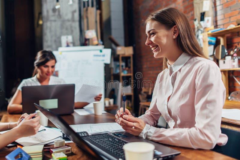 Equipe das mulheres de neg?cio que trabalham com pap?is usando os port?teis que sentam-se na mesa no escrit?rio foto de stock royalty free