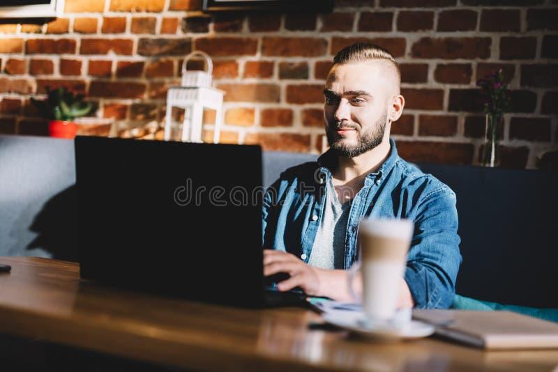 Equipe a datilografia em um portátil em um café imagem de stock