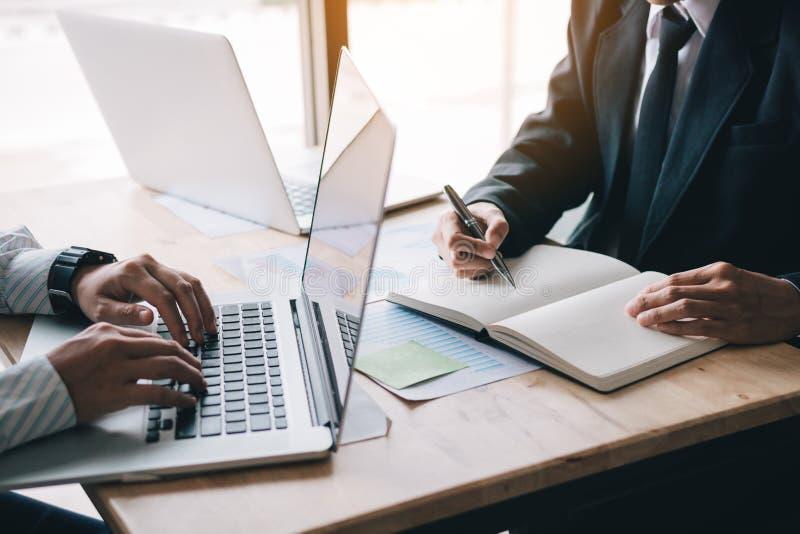 A equipe de dois homens de negócios calcula sobre o anuário do relatório sumário no escritório da tabela foto de stock royalty free