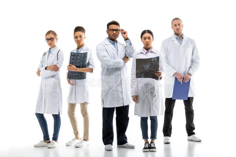 Equipe de doutores profissionais novos nos revestimentos brancos que estão junto imagens de stock