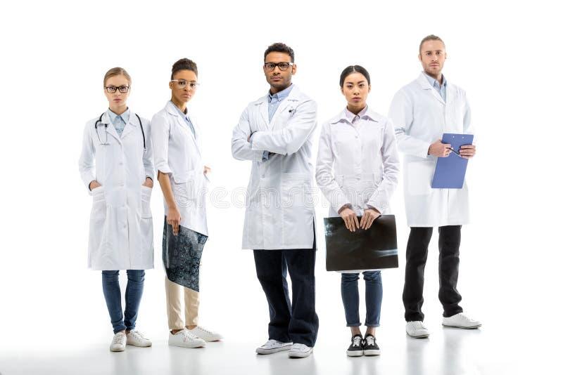 Equipe de doutores profissionais novos nos revestimentos brancos que estão junto foto de stock