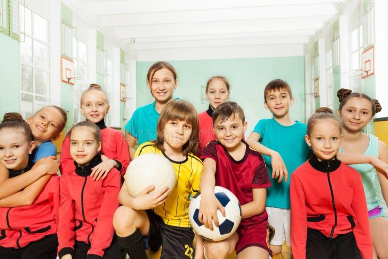 Equipe de futebol do ` s das crianças no salão de esportes da escola foto de stock royalty free