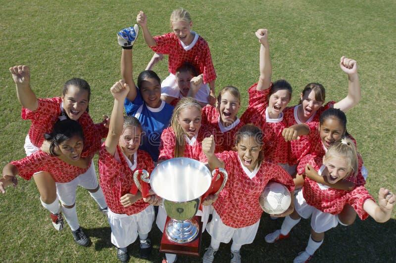 Equipe de futebol fêmea que guardara o troféu imagens de stock