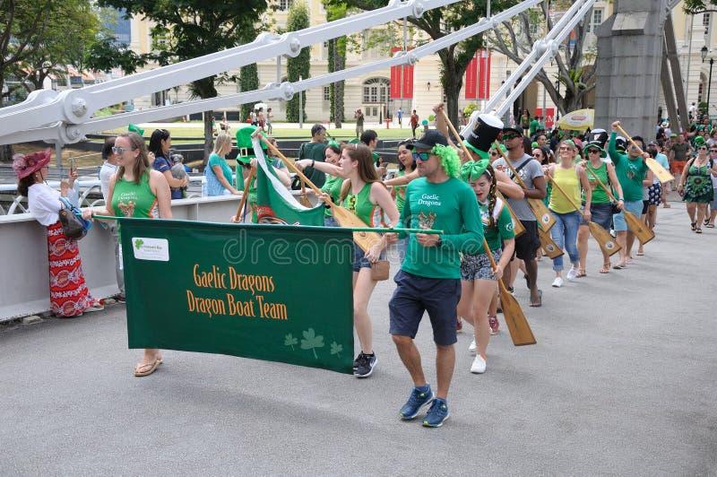 Equipe de Gaelic Dragon do dia do ` s de St Patrick que cruza a ponte de Cavengah em Singapura fotografia de stock royalty free
