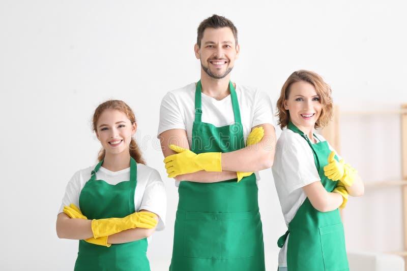 Equipe de profissionais novos do serviço da limpeza no trabalho fotografia de stock