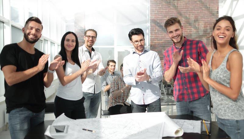 A equipe de projeto deu uma aclamação de pé no escritório criativo foto de stock