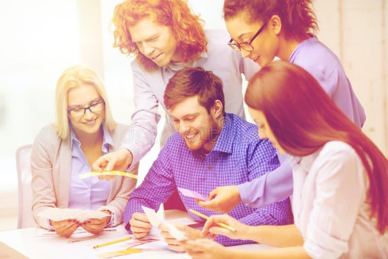 Equipe de sorriso com as amostras da cor no escritório imagens de stock