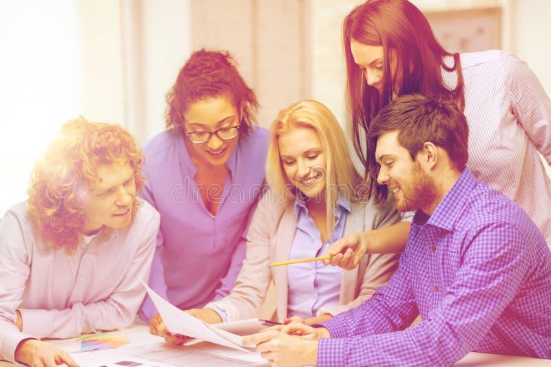 Equipe de sorriso com as amostras da cor no escritório fotografia de stock