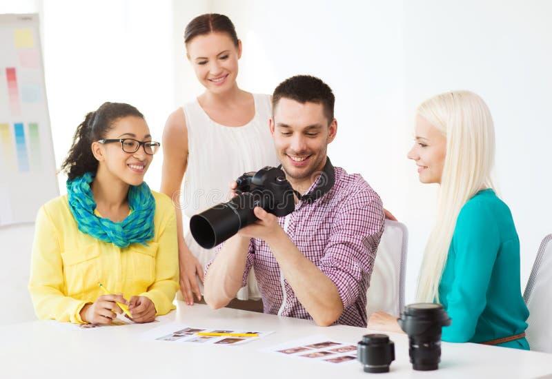 Equipe de sorriso com o photocamera que trabalha no escritório fotografia de stock royalty free