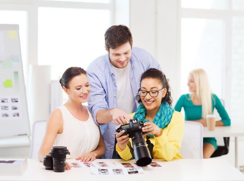 Equipe de sorriso com o photocamera que trabalha no escritório fotografia de stock