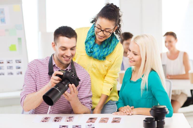 Equipe de sorriso com o photocamera que trabalha no escritório fotos de stock