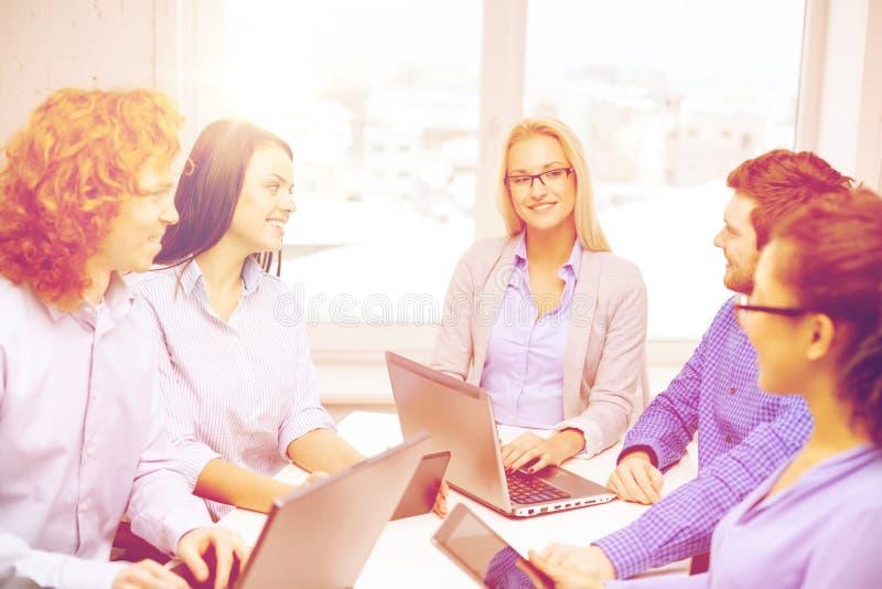 Equipe de sorriso com os computadores do PC do portátil e da tabela fotos de stock