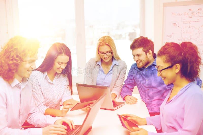 Equipe de sorriso com os computadores do PC do portátil e da tabela fotografia de stock royalty free