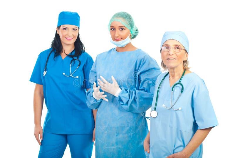 Equipe de sorriso de três mulheres dos cirurgiões fotografia de stock