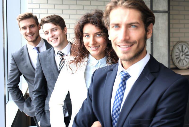 Equipe de sorriso feliz do negócio que está em seguido no escritório fotografia de stock royalty free