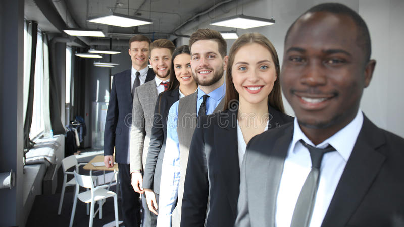 Equipe de sorriso feliz do negócio que está em seguido no escritório imagens de stock royalty free