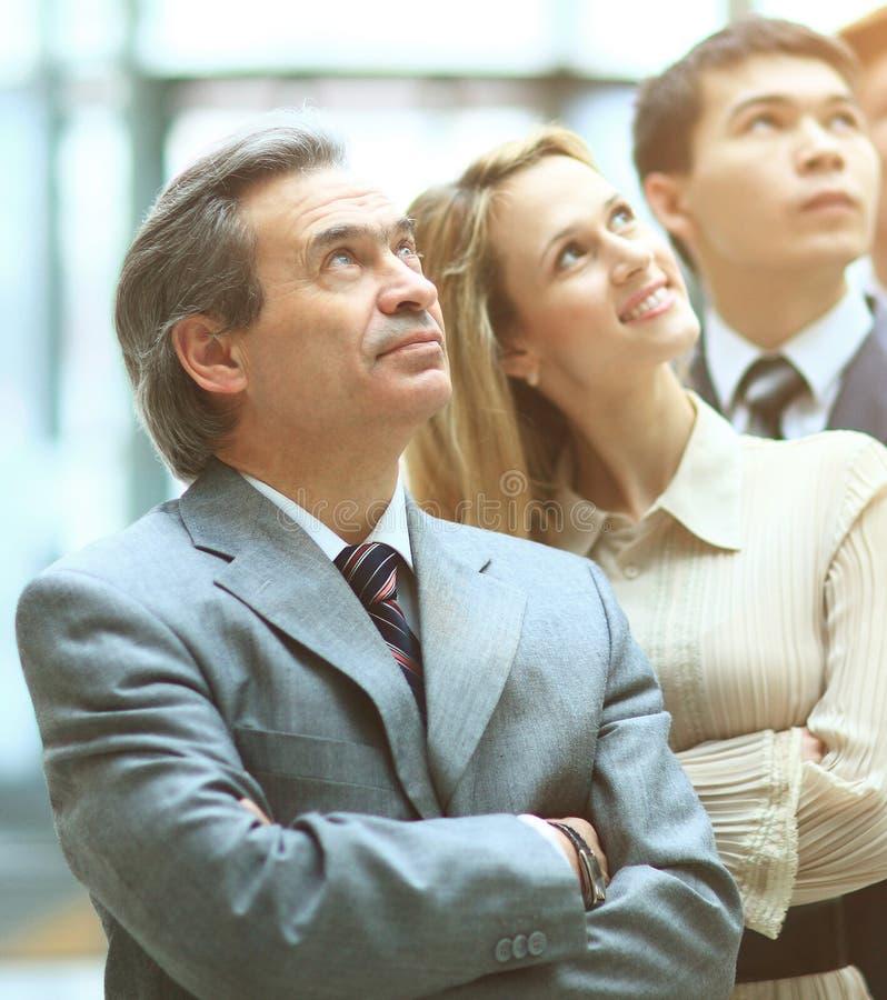 Equipe de sorriso feliz do negócio que está em seguido no escritório e que olha acima à propaganda virtual imagens de stock